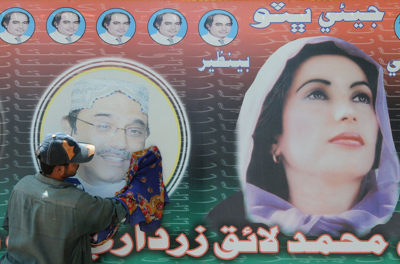 """De Pakistaanse presidentskandidaat Asif Ali Zardari op een verkiezingsposter met zijn in december vermoorde echtgenote Benazir Bhutto, in de stad Nawabshah.Foto AFP ==== TO GO WITH """"PAKISTAN-VOTE-ZARDARI-HOME"""" by Hasan Mansoor In this picture taken on September 2, 2008, an employee of Asif Ali Zardari, the widower of slain former prime minister Benazir Bhutto cleans a poster of Zardari outside his under construction house in Nawabshah. In the extreme heat that allows sugarcane and banana to flourish in the fields surrounding Nawabshah, workers are busy building """"Zardari House"""", a home for Pakistan's likely next president. The mansion is rising in one of this southern city's poshest suburbs, with labourers working around the clock to ensure it will befit its eponymous incumbent. AFP PHOTO/Rizwan TABASSUM"""