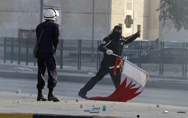 "A policeman confronts a protester in the Shi'ite village Sanabis near Manama February 14, 2011. Bahraini police fired teargas and rubber bullets to break up protests on Monday in Shi'ite villages that ring the capital Manama, dampening a ""Day of Rage"" stimulated by popular upheaval in Egypt and Tunisia. REUTERS/Hamad I Mohammed (BAHRAIN - Tags: POLITICS CIVIL UNREST)"