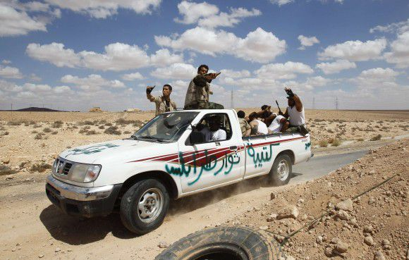 A group of pro-Gaddafi soldiers, with their hands tied behind their backs after they were captured by anti-Gaddafi forces outside Libya's besieged city of Bani Walid, are being driven in the back of a pickup truck following clashes on the frontline September 9, 2011. REUTERS/Zohra Bensemra (LIBYA - Tags: POLITICS CONFLICT MILITARY)