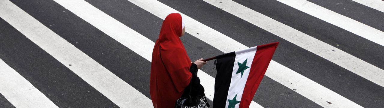 An Arab demonstrator holds a Syrian flag in a demonstration to protest the military crackdown in Syria, in downtown Sao Paulo July 3, 2011. REUTERS/Nacho Doce (BRAZIL - Tags: POLITICS CIVIL UNREST)