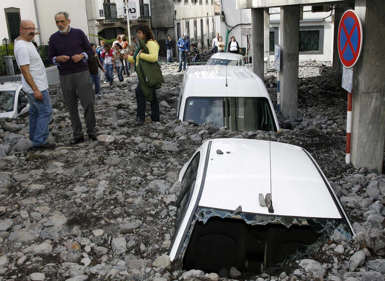 People view a destroyed downtown Funchal street as cars lay buried under debris after heavy flooding in Madeira island February 21, 2010. Portuguese rescue workers using bulldozers searched on Sunday for more bodies under debris after violent floods and mudslides killed at least 40 on the resort island of Madeira. REUTERS/Duarte Sa (PORTUGAL - Tags: DISASTER ENVIRONMENT TRANSPORT)