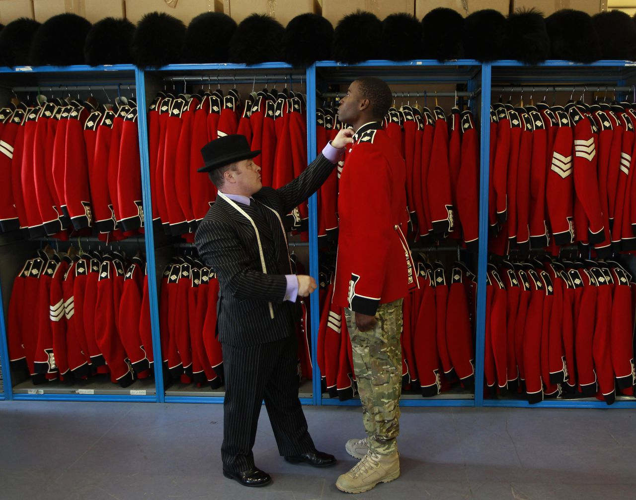Irish Guardsman Bortnill St'Ange is fitted with his ceremonial uniform by Master Tailor Lance Sergeant Matthew Else at their barracks in Windsor, southern England April 21, 2011. The Guards will perform ceremonial duties at the wedding of Britain's Prince William and Kate Middleton on April 29. REUTERS/Eddie Keogh (BRITAIN - Tags: ROYALS MILITARY SOCIETY)