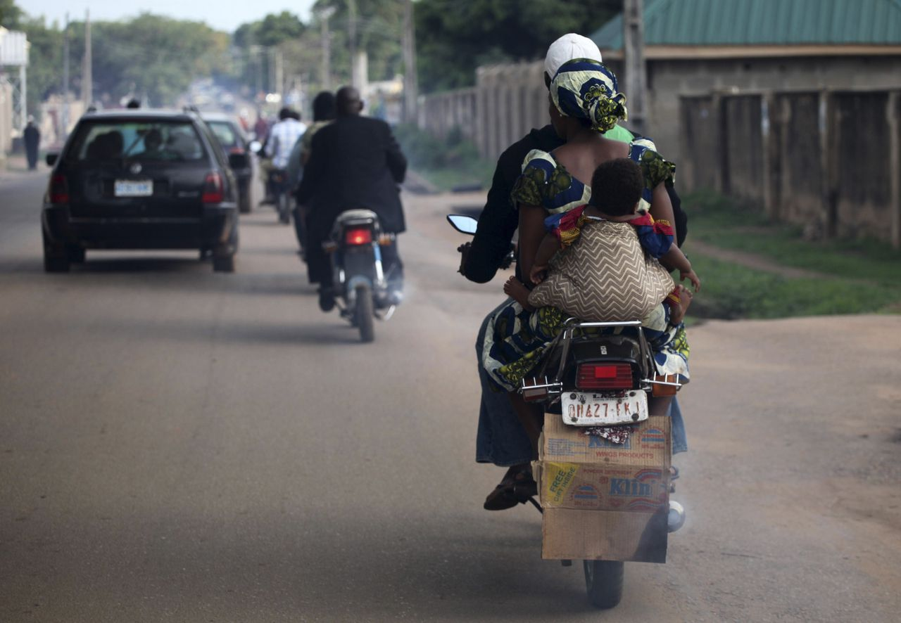 A woman commutes on a motorcycle taxi with her child wrapped on her back in Nigeria's northern city of Kaduna May 29, 2012.REUTERS/Akintunde Akinleye(NIGERIA - Tags: SOCIETY TRANSPORT)