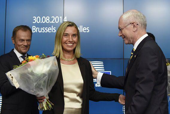 Van Rompuy feliciteert Federica Mogherini. Op de achtergrond: Donald Tusk.
