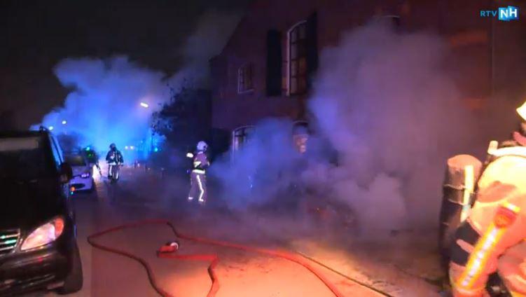 Brandweerlieden blussen de brandende auto's.