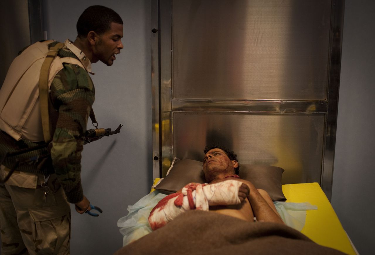 An injured captured soldier loyal to Libyan leader Moammar Gadhafi is interrogated by a rebel soldier at the Jalaa hospital in Benghazi, eastern Libya, Saturday, March 19, 2011. In the hours before the no-fly zone over Libya went into effect, Gadhafi sent warplanes, tanks and troops into Benghazi, the rebel capital and first city to fall to the rebellion that began Feb. 15. Then the government attacks appeared to go silent. (AP Photo/Anja Niedringhaus)