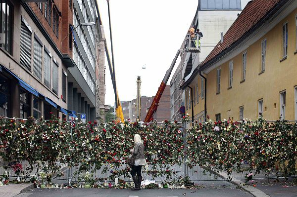 A woman places flowers on a fence in respect of the victims in last Friday's killing spree and bomb attack, in Oslo July 27, 2011. Norway's prime minister on Wednesday pledged a security review after a mourning period for at least 76 people killed by a far-right zealot in bombing and shooting attacks that have traumatised the nation. REUTERS/Cathal McNaughton (NORWAY - Tags: CRIME LAW CIVIL UNREST POLITICS)