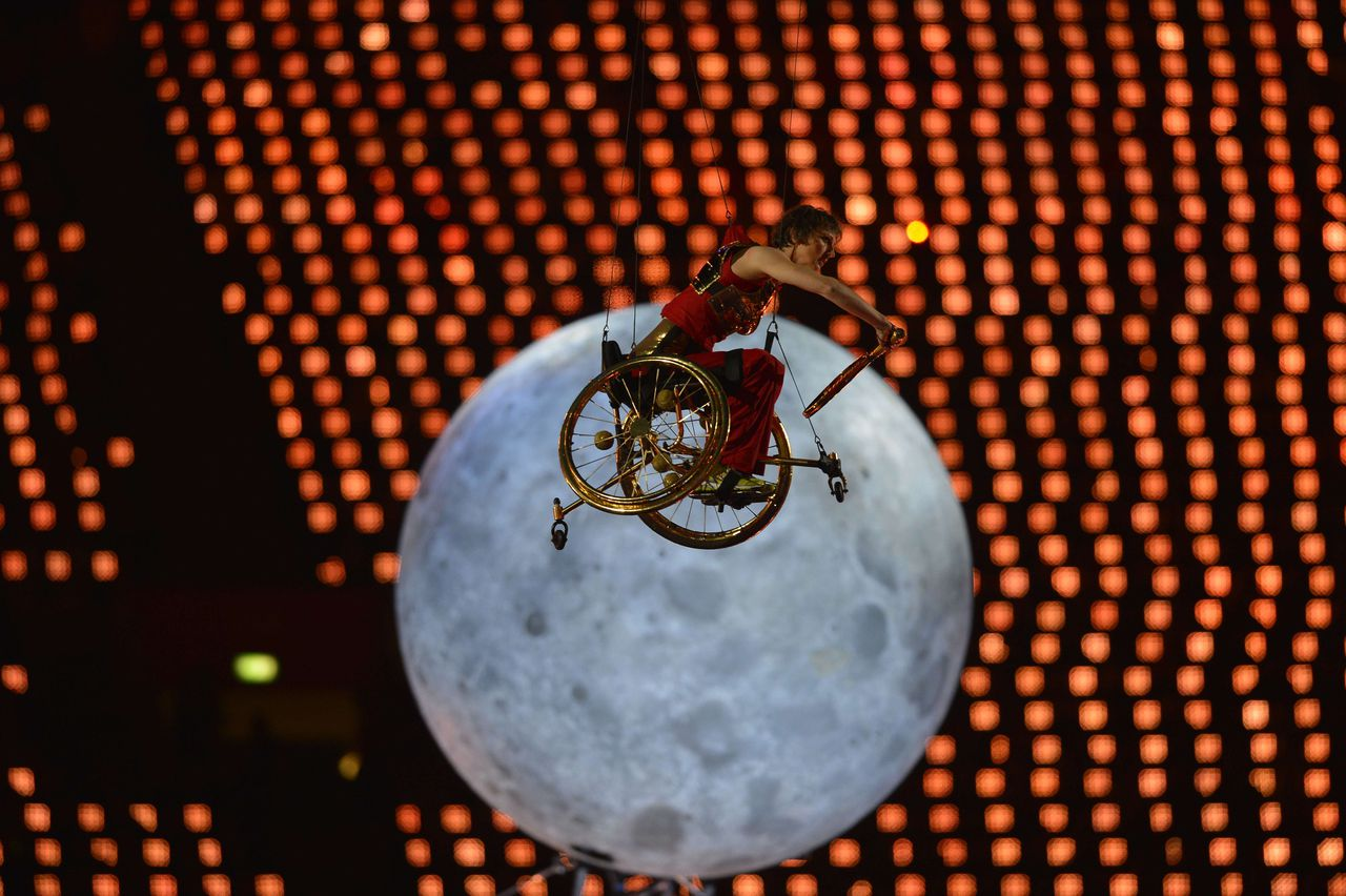 A wheelchair tennis player glides on wires above the arena during the opening ceremony of the London 2012 Paralympic Games at the Olympic Stadium in east London on August 29, 2012. AFP PHOTO / LEON NEAL