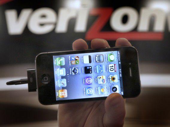 Een winkelmanager van Verizon houdt een iPhone omhoog.