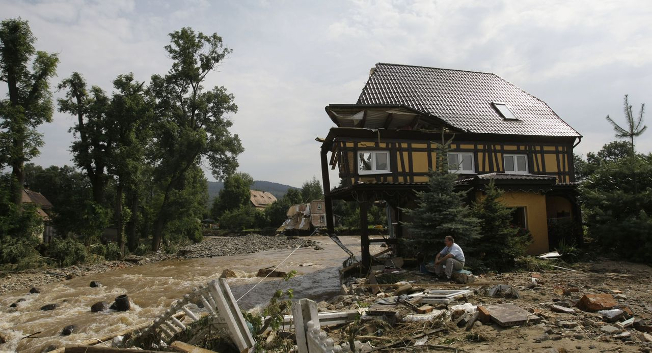 Inwoners van het Poolse plaatsje Bogatynia zitten bij hun door een overstroming verwoeste huis. In Bogatynia verdronken twee mensen. Foto AP A resident sits by his destroyed house after a flash floods hit the town of Bogatynia, Poland, Sunday, Aug. 8, 2010. The flooding has struck an area near the borders of Poland, Germany and the Czech Republic. (AP Photo/Petr David Josek)