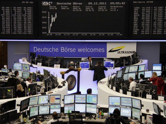 Traders are pictured at their desks in front of the DAX board at the Frankfurt stock exchange December 9, 2011. REUTERS/Remote/Kirill Iordansky (GERMANY - Tags: BUSINESS)