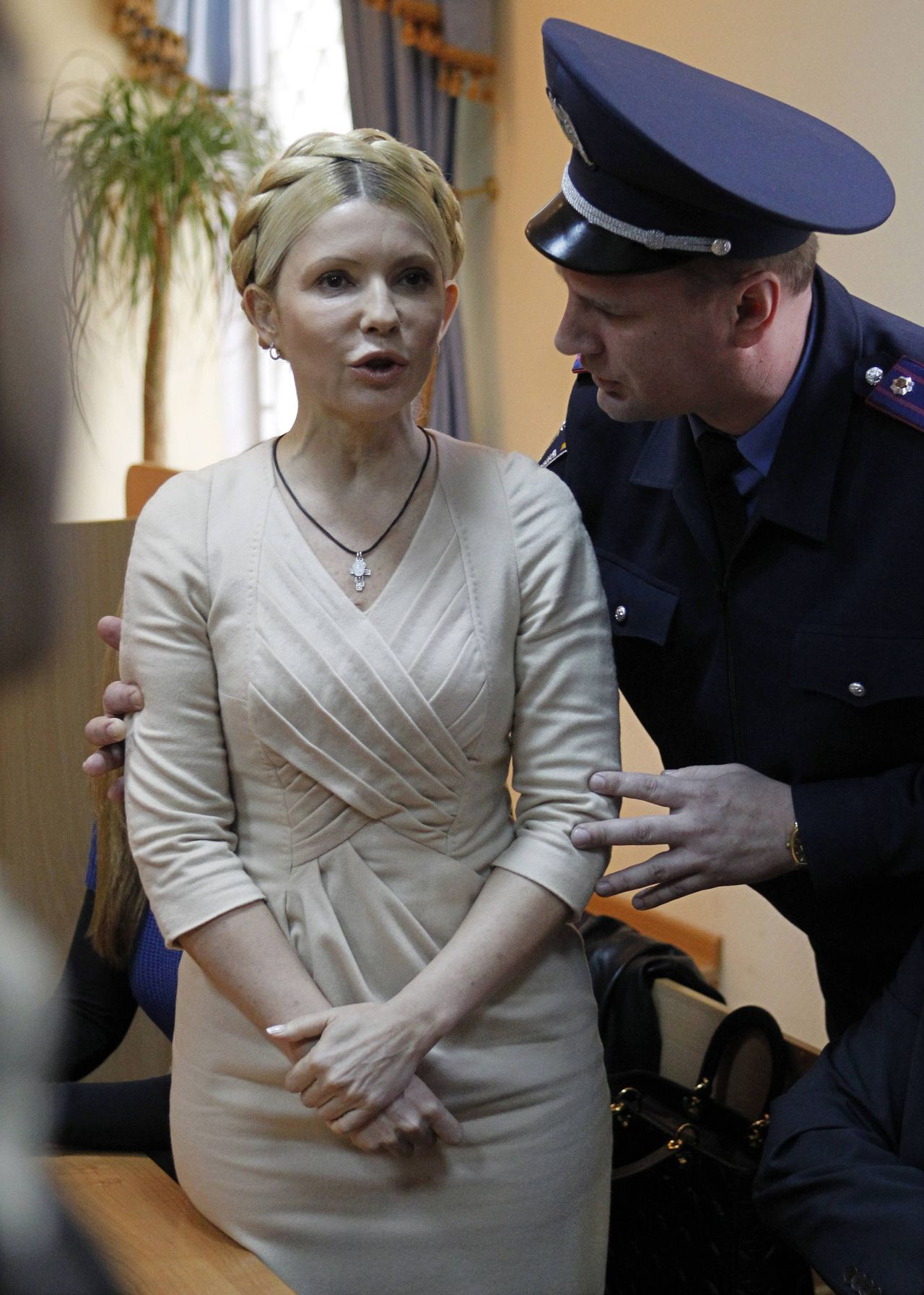 An Interior Ministry officer asks Ukrainian ex-prime minister Yulia Tymoshenko (L) to keep quiet while judge Rodion Kireyev reads the verdict during a session at the Pecherskiy district court in Kiev October 11, 2011. A Ukrainian court on Tuesday sentenced former prime minister Yulia Tymoshenko to seven years in prison for abuse of office in relation to a 2009 gas deal with Russia that she brokered, a case regarded widely in the West as politically orchestrated. REUTERS/Gleb Garanich (UKRAINE - Tags: CRIME LAW POLITICS)