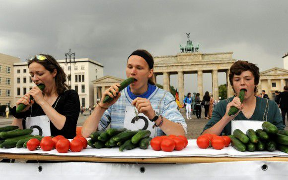 (L-R) Kati Brunne, Felix Albrecht and Lewin Grabo take part in a cucumber eating contest on June 14, 2011 in front of the Brandenburg Gate in Berlin. Germany's vegetarian's association staged the action to acquit cucumbers, tomatoes and salad from the suspicion of being the source of the deadly E. coli bacteria outbreak. The death toll from the killer bacteria outbreak rose to 36 on June 13, 2011 as Germany said a warning to avoid eating cucumbers, lettuce and tomatoes, initially suspected of carrying the bug, had seen up to 10 percent of crops destroyed. AFP PHOTO MAURIZIO GAMBARINI GERMANY OUT