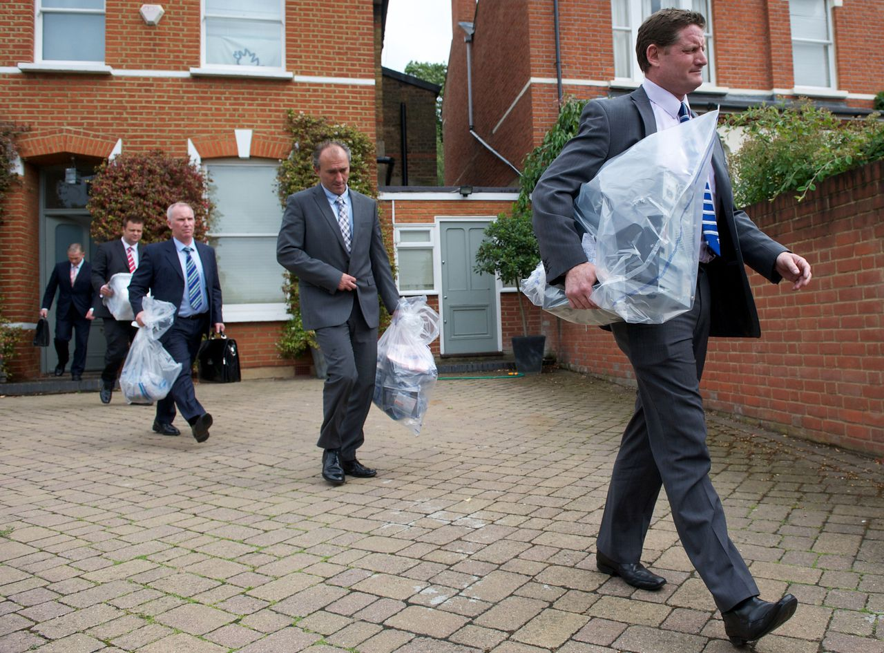Plain clothes policemen carry plastic bags of evidence as they leave the home of Andy Coulson, the former media chief of British Prime Minister David Cameron, in London, on July 8, 2011. Police arrested David Cameron's ex-media chief over Britain's phone hacking scandal on Friday as the prime minister promised urgent inquiries into failures by politicians, police and the press. Cameron appeared rattled at the toughest press conference of his year in power, but still defended hiring Andy Coulson, the former editor of the Rupert Murdoch-owned News of the World tabloid, which is now to shut. AFP PHOTO / ANDREW COWIE