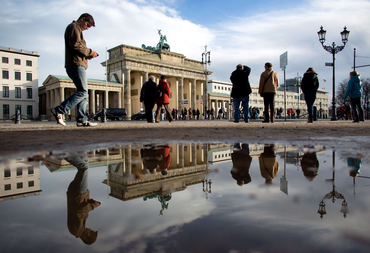 A man checks his mobile device as he passes Berlin's landmark Brandenburg Gate that is mirrored in a puddle on November 04, 2012 in Berlin, Germany. AFP PHOTO / KAY NIETFELD GERMANY OUT