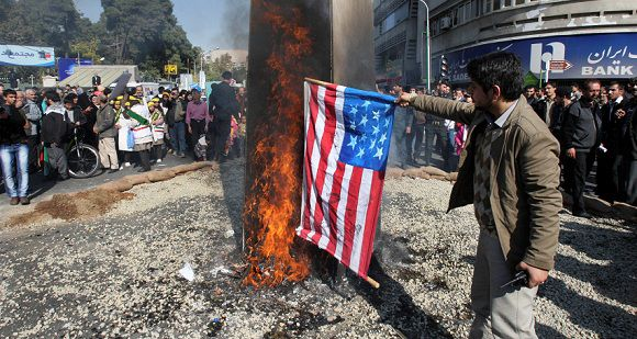 Caption: A man sets on fire a representation of a US flag, in an annual state-backed rally in front of the former US Embassy in Tehran, Iran, Friday, Nov. 4, 2011, marking the anniversary of the seizure of the US Embassy by militant students on Nov. 4, 1979, when militant Iranian students who believed the embassy was a center of plots against the Persian country held 52 Americans hostage for 444 days. The US severed diplomatic ties in response, and the two countries have not had formal relations since. (AP Photo/Vahid Salemi)