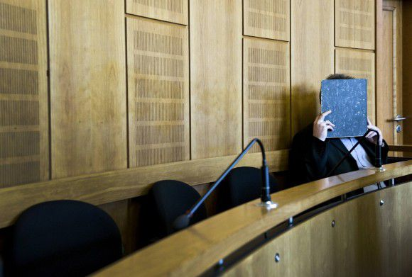 Defendant Olaf H. covers his face in the regional court in Krefeld, September 19, 2011. The trial of Olaf H., accused of killing 10-year old Mirco S., who went missing since September 3, 2010 and was found after 146 days of searches, continued on Monday. REUTERS/Victoria Bonn-Meuser/Pool (GERMANY - Tags: CRIME LAW)