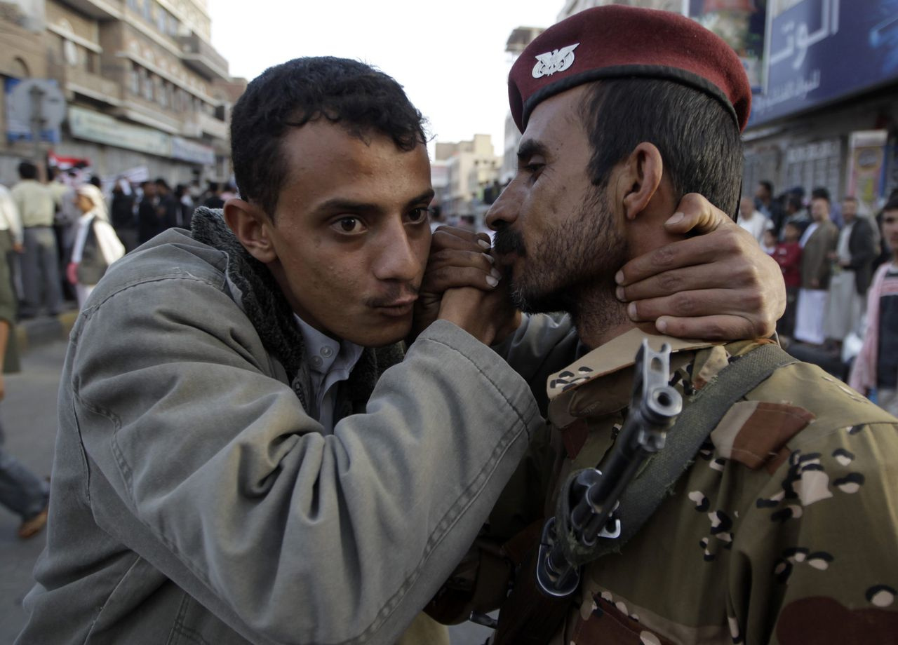 A Yemeni army soldier is kissed by a demonstrator while standing guard to protect anti-government protesters during a demonstration demanding the resignation of Yemeni President Ali Abdullah Saleh in Sanaa April 4, 2011. Police and armed men in civilian clothes opened fire on anti-government demonstrators in the Yemeni cities of Taiz and Hudaida on Monday, witnesses said, as a drive to oust President Ali Abdullah Saleh gathered pace.REUTERS/Ammar Awad (YEMEN - Tags: POLITICS CIVIL UNREST)