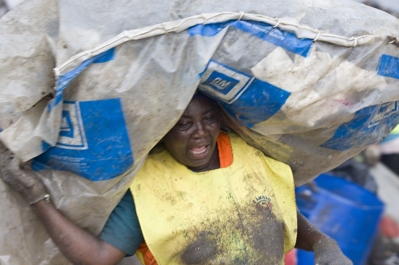 """Een vrouw op de Gramacho-vuilnisbelt bij Rio de Janeiro. Foto AFP TO GO WITH AFP STORY A woman carries on her head a bag full of trash like the other three thousand people who work at the Gramacho garbage dump, near the Guanabara bay, on November 6, 2008 in Rio de Janeiro, Brazil. Due to ecological problems the 1,300,000 square meter garbage deposit is going to be closed, threatening the USD 470 average income of each one of the """"miners"""" that work in the 55-meter-high hill of garbage selecting recyclable material like glass, paper and plastic amid the city trash. AFP PHOTO ANTONIO SCORZA"""