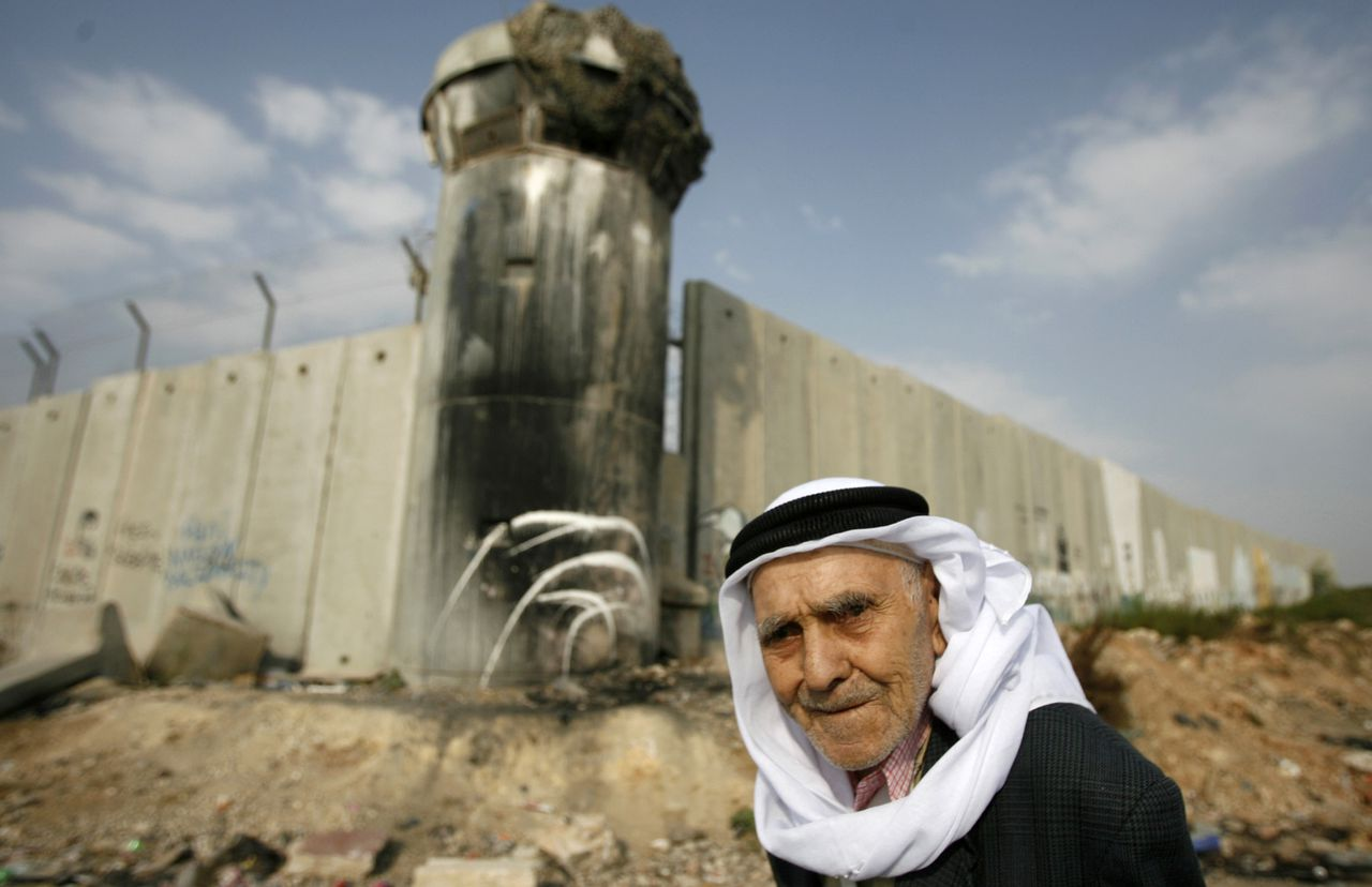 De muur die Israël heeft gebouwd aan de grens met Palestijns gebied maakt het land tot een enclave in de regio. foto reuters A Palestinian man walks near the controversial Israeli barrier as he crosses the Qalandiya checkpoint outside the West Bank city of Ramallah September 5, 2008, on his way to the al-Aqsa mosque in Jerusalem on the first Friday of the Muslim holy month of Ramadan. REUTERS/Fadi Arouri (WEST BANK)