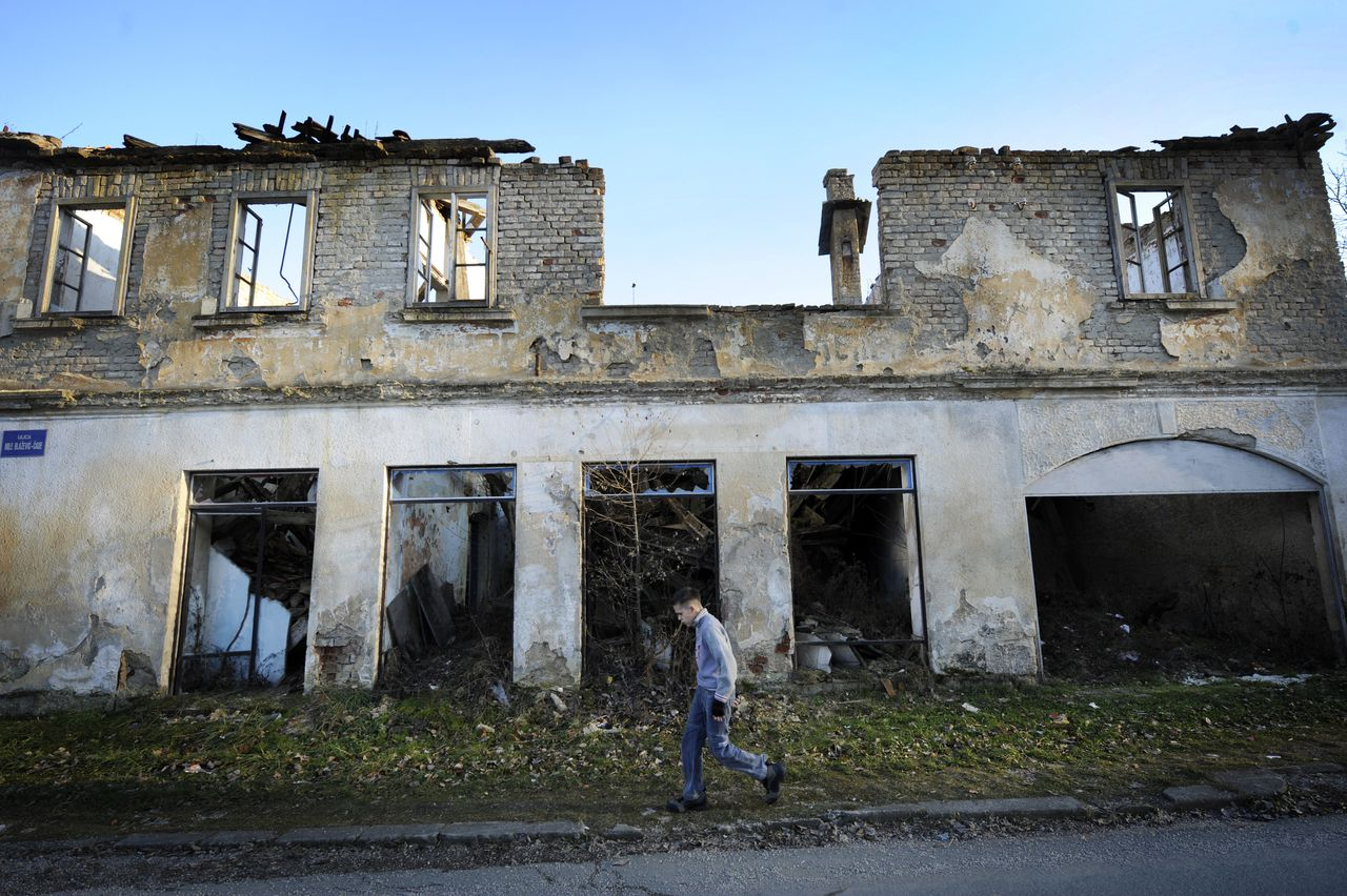 A boy walks past a building destroyed in the 1991-1995 Serbo-Croatian war, on January 18, 2011 in the central Croatian town of Dvor. Croatian Serbs, whose rights were among key criteria for Zagreb's EU bid, hope that its entry in the bloc, on which the country votes in a referendum on January 21, could further affirm their minority. The region of Dvor, some 120 kilometers (78 miles) southeast of Zagreb, on the Una river marking the border with Bosnia, was captured by Serbs during the war. Croatians fled at the start of the conflict and Serbs after it ended. AFP PHOTO / HRVOJE POLAN