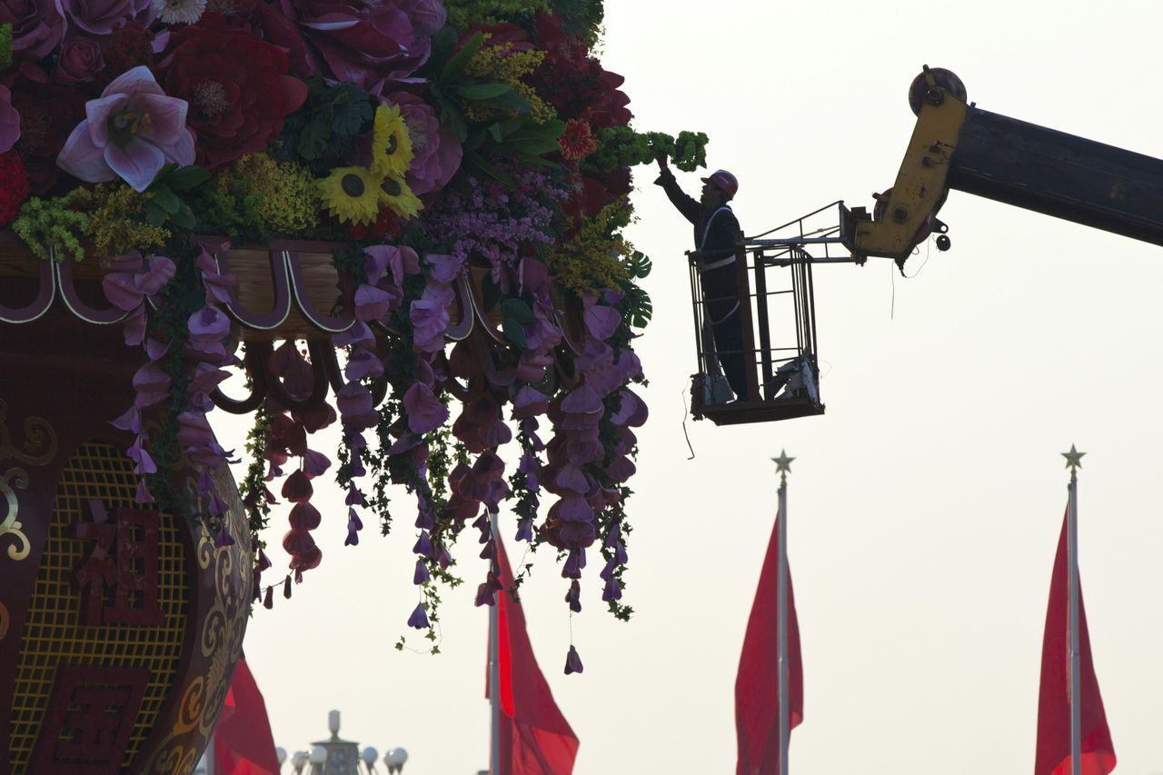 A worker changes fake bouquets of a giant flower basket at Tiananmen Square in Beijing, China, Tuesday, Nov. 6, 2012. The Chinese Communist Party will hold it's 18th National Congress on Thursday, Nov. 8, 2012. The once-a-decade event will install new leadership to run the world's second largest economy and newly assertive global power. (AP Photo/Alexander F. Yuan)
