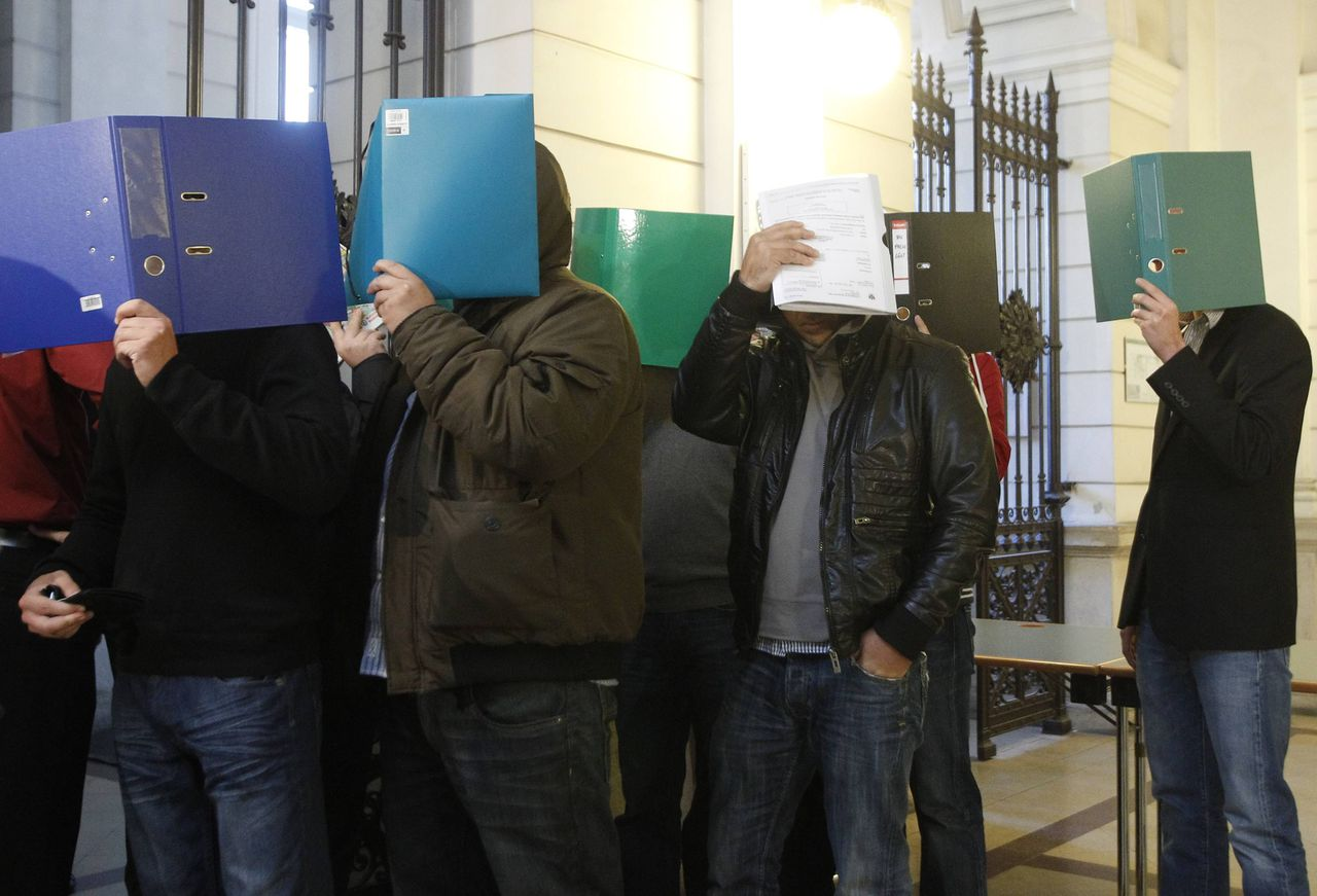 Defendants, part of a group of 85 supporters of SK Rapid who are accused of rioting, wait to stand in front of the court in Vienna October 3, 2011. The supporters are accused of rioting as they waited for supporters of rival club FK Austria to return from a match on May 21, 2009. REUTERS/Lisi Niesner (AUSTRIA - Tags: CRIME LAW SPORT SOCCER)