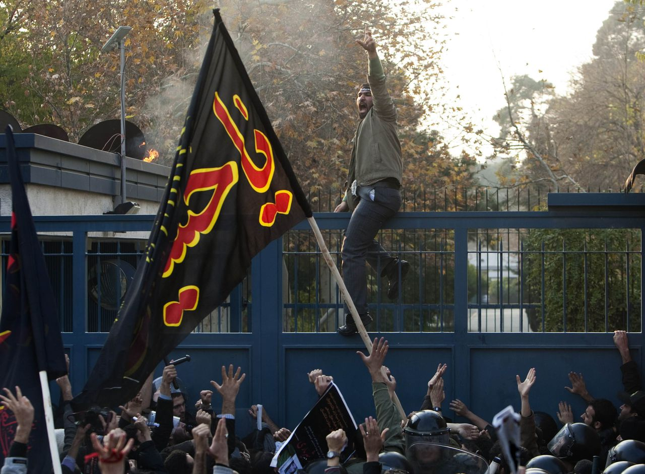 EDITORS' NOTE: Reuters and other foreign media are subject to Iranian restrictions on leaving the office to report, film or take pictures in Tehran. Iranian protesters shout slogans as one of the protesters climbs over the gate of the British embassy in Tehran November 29, 2011. Iranian protesters stormed two British Embassy compounds in Tehran on Tuesday, smashing windows, hurling petrol bombs and burning the British flag in a protest against sanctions imposed by Britain, live Iranian television showed. REUTERS/Raheb Homavandi (IRAN - Tags: POLITICS CIVIL UNREST)