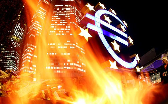 Caption: FILE - In this Nov. 21, 2011 file picture taken with a fisheye lens, flames from a fire set alight in a container by activists of the Frankfurt Occupy movement are seen in front of the European Central Bank and a sculpture of the euro symbol in Frankfurt, Germany. Austerity has been the main prescription across Europe for dealing with the continent's nearly 3-year-old debt crisis, brought on by too much government spending. (AP Photo/Michael Probst,File)
