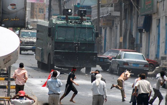 Protestors throw rocks at an anti-riot vehicle during clashes with security forces, in Taiz, Yemen,