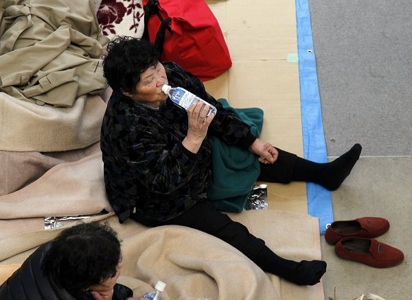 An evacuee drinks from a bottled water at a shelter in Koriyama city in Fukushima prefecture, 60km west of Tokyo on March 23, 2011. The Japanese government told people not to drink tap water in a village near the quake-hit nuclear power plant after high levels of radioactive iodine were detected. AFP PHOTO / Ken SHIMIZU