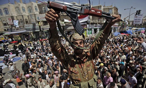 A Yemeni army officer reacts holding up his AK-47 as he and other officers join anti-government protestors demanding the resignation of Yemeni President Ali Abdullah Saleh, in Sanaa,Yemen, Monday, March 21, 2011. Three Yemeni army commanders, including a top general, defected Monday to the opposition calling for an end to President Ali Abdullah Saleh's rule, as army tanks and armored vehicles deployed in support of thousands protesting in the capital. With the defection, it appeared Saleh's support was eroding from every power base in the nation _ his own tribe called on him to step down, he fired his entire Cabinet ahead of what one government official said was a planned mass resignation, and his ambassador to the U.N. and human rights minister quit. (AP Photo/Muhammed Muheisen)