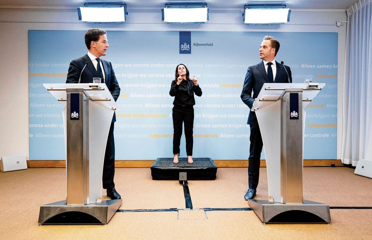 De persconferentie, woensdag, van premier Rutte en minister De Jonge. Tussen hen in doventolk Irma Sluis.