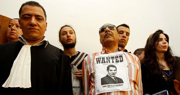 """A sign that reads """"Wanted for Dictatorship"""" is stuck on the shirt of a protester inside a courtroom on the opening day of the trial in absentia of Tunisia's ousted president Zine al-Abidine Ben Ali and his wife Leila in Tunis June 20, 2011. Ben Ali said on Monday he was tricked into leaving the country six months ago, setting the stage for a revolution which inspired the """"Arab Spring"""" rippling across the region. REUTERS/Zoubeir Souissi (TUNISIA - Tags: POLITICS CRIME LAW CIVIL UNREST)"""