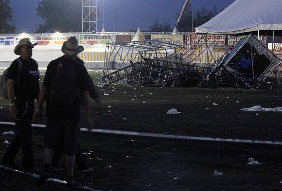 Volunteers look at the wreckage of a tent which collapsed following a heavy storm at the Pukkelpop outdoor music festival near Hasselt, northern Belgium, August 18, 2011. Two people were killed after a storm ripped through a pop music festival in Belgium on Thursday. Another 40 festival-goers were injured when a burst of high winds and heavy rain collapsed tents and felled a tree, officials said. REUTERS/Sebastien Pirlet (BELGIUM - Tags: DISASTER)