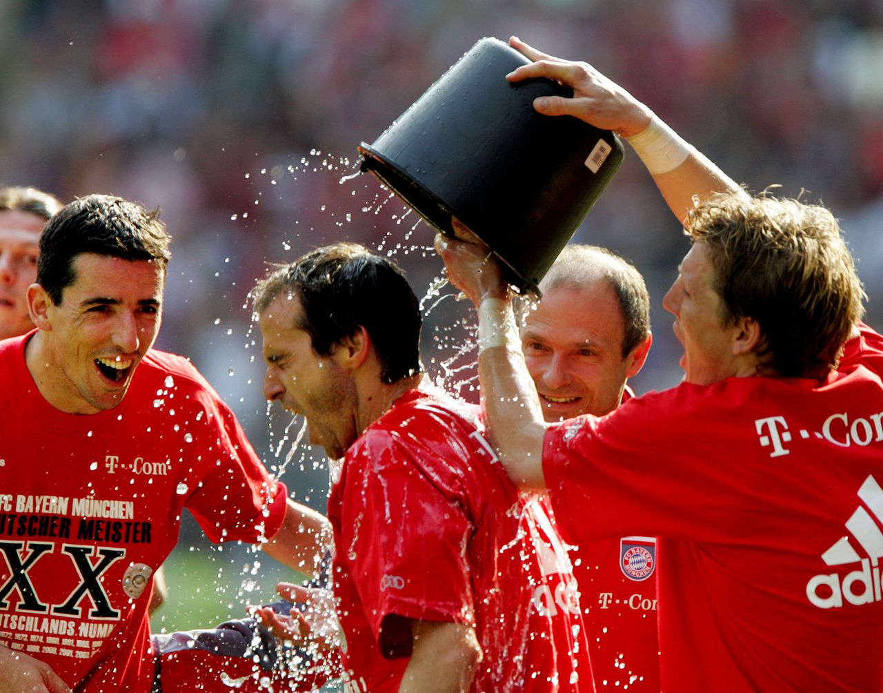 Spelers Bastian Schweinsteiger, Mehmet Scholl en Ron Makaay van Bayern München vieren de landstitel, afgelopen zaterdag. Foto AP Munich players Bastian Schweinsteiger, Mehmet Scholl and Roy Makaay of Netherlands, from right, celebrate with water after the German first soccer division between 1. FC Kaiserslautern and Bayern Munich in the Fritz-Walter stadium in Kaiserslautern, southern Germany, Saturday, May 6, 2006. Bayern Munich clinched its 20th German title by drawing 1-1 at FC Kaiserslautern on Saturday.(AP Photo/Michael Probst)** EMBARGOED AGAINST ANY MOBILE USE (NO MMS) UNTIL 18:30 GMT **