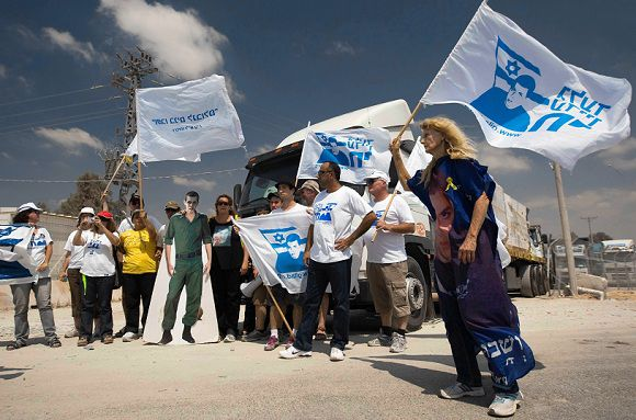 Caption: Israeli activists block a truck bearing goods destined for the Gaza Strip during a protest at the Kerem Shalom border crossing, August 28, 2011, to mark the 25th birthday of captured Israeli soldier Gilad Shalit. Shalit was captured by Palestinian militants who tunnelled from the Gaza Strip into southern Israel in June 2006. REUTERS/Amir Cohen (ISRAEL - Tags: POLITICS CIVIL UNREST)