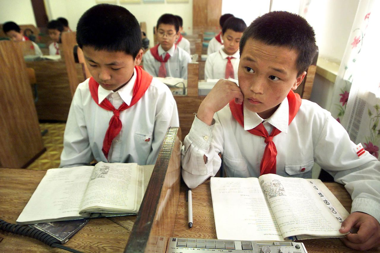 Kinderen in de klas op een basisschool in Pyongyang, Noord-Korea. Goed onderwijs vergroot de kans dat een niet-democratisch land een democratie wordt. foto afp North Korean students listen and read along with their teacher during English language class, 03 May 2001 in Pyongyang's Moran Primary School #1. Despite North Korea's state-controlled press continually berating the United States as enemy number one, a teacher admitted that English is one of the most powerful tools she can give her young pupils in preparing them to deal with the complex world ahead of them. AFP PHOTO/Stephen SHAVER