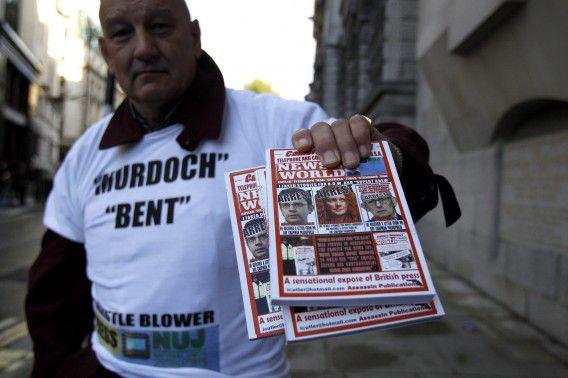 Een man demonstreert buiten de Old Bailey in Londen, maandag, bij aanvang van het proces tegen onder anderen Rebekah Brooks en Andy Coulson.