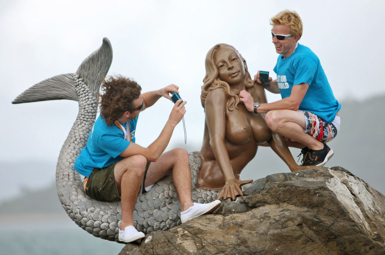"""The Best Job in the World"" competition finalists George Karellas (L) of Ireland and Ben Southall of Britain sit on a mermaid statue during a media opportunity on Daydream Island, about 950km (590 miles) north of Brisbane, May 5, 2009. Karellas and Southall are two of 16 finalists from 15 nations in the tourism promotion competition aimed at attracting visitors to Australia's northeast tropical state of Queensland. The winner will earn A$150,000 ($110,000) in the role of ""Island Caretaker"" on the Great Barrier Reef for six months. REUTERS/Tourism Queensland/Eddie Safarik/Handout (AUSTRALIA EMPLOYMENT BUSINESS TRAVEL SOCIETY) FOR EDITORIAL USE ONLY. NOT FOR SALE FOR MARKETING OR ADVERTISING CAMPAIGNS"