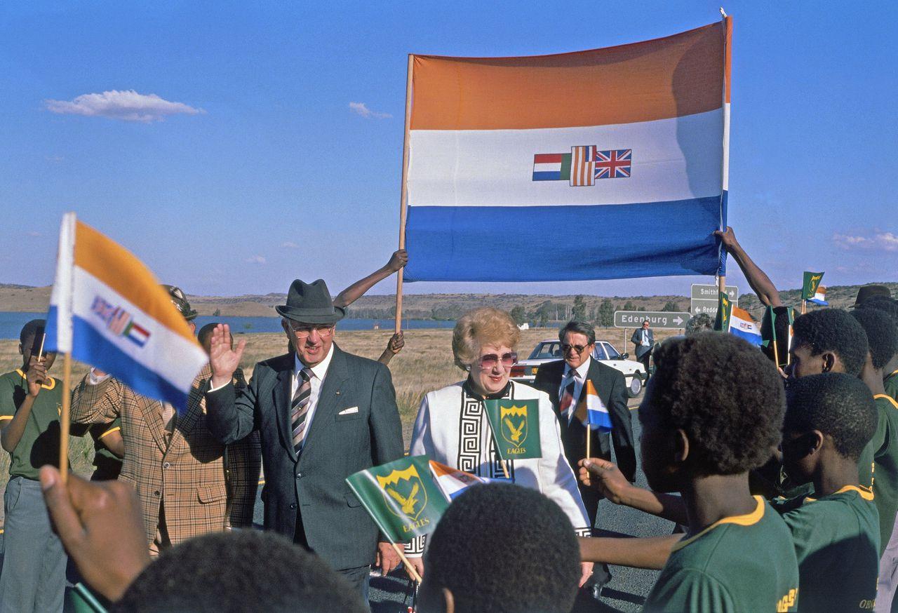 De Zuid-Afrikaanse president Pieter Willem Botha bij een openbaar optreden in 1989. Op de achtergrond wordt de apartheidsvlag opgehouden.