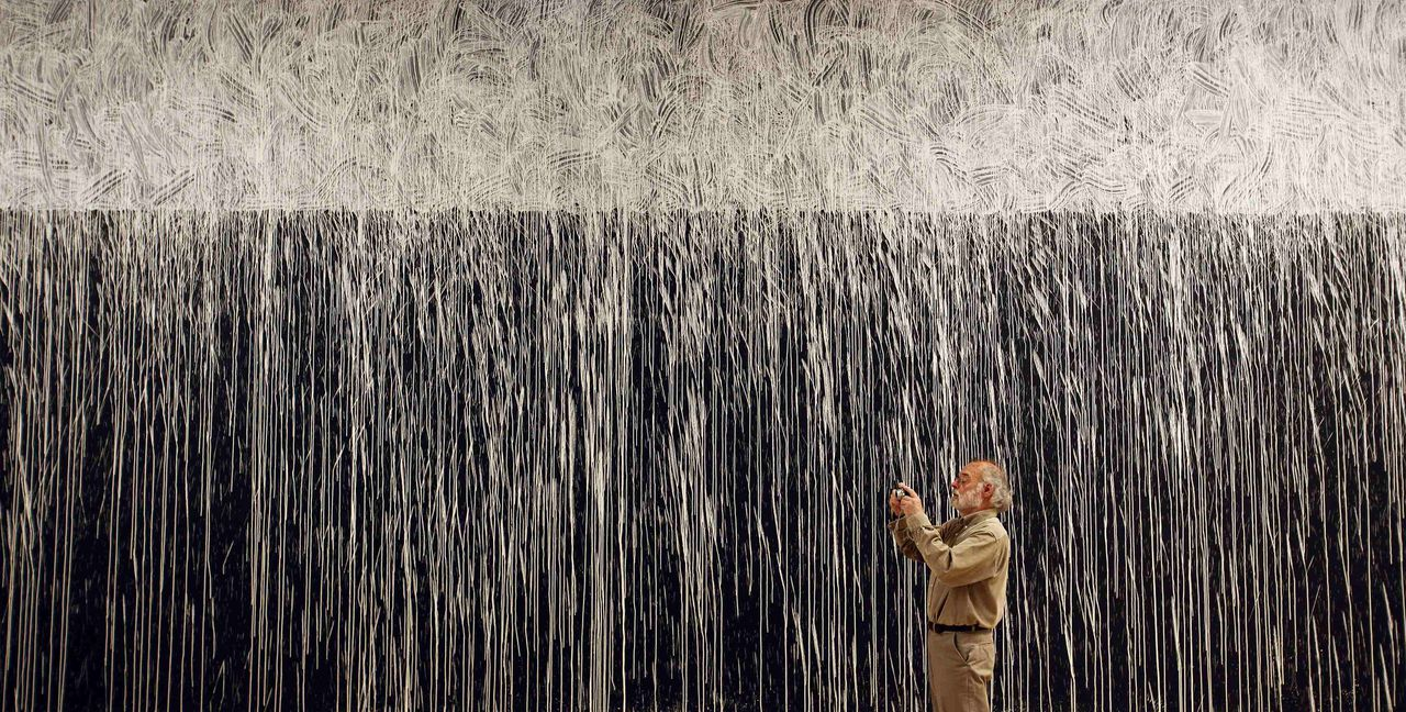 Een toeschouwer staat voor het werk White Water Line van kunstenaar Richard Long in de Tate Britain gallery in Londen. Foto Reuters. A man takes a picture in front of 'White Water Line' by British artist Richard Long during a media preview of his exhibition Heaven and Earth at the Tate Britain gallery in London June 1, 2009. REUTERS/Stefan Wermuth (BRITAIN SOCIETY)