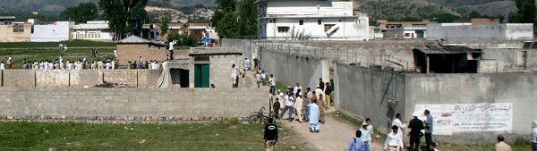 Caption: Local people and news media gather round the compound and house, seen on right, of Osama bin Laden as authorities eased the security and allowed people to approach the perimeter of the compound in Abbottabad, Pakistan, on Tuesday, May 3, 2011, after a U.S. military raid late Monday which ended with the death of the al-Qaida leader Osama bin Laden and others inside the compound. U.S. Navy SEALs swept through the massive compound Monday in pursuit of their target, bin Laden, and it is revealed Tuesday by White House counterterrorism adviser John Brennan that the U.S. already was scouring through items seized in the raid, said to include hard drives, DVD's, a pile of documents and other items. (AP Photo/Aqeel Ahmed)