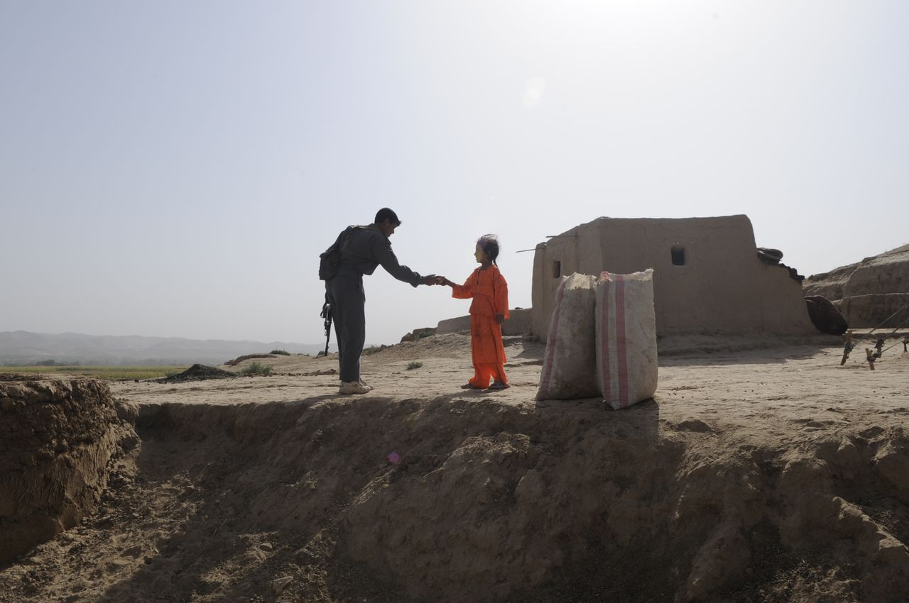 BALA MURGHAB, Afghanistan- An Afghan National Police member receives water from a local village girl during an International Security Assistance Force (ISAF) humanitarian mission near Forward Operating Base (FOB) Bala Murghab, Oct. 3, 2008.