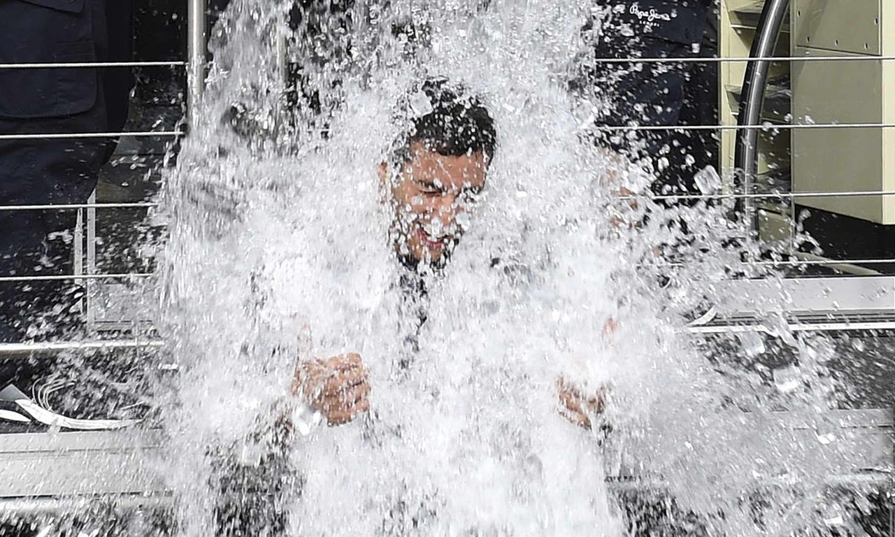 """Red Bull Racing team members dump a bucket of ice water onto Formula One driver Daniel Ricciardo of Australia as he takes part in the """"Ice Bucket Challenge"""" ahead of the Belgian F1 Grand Prix in Spa-Francorchamps August 21, 2014. Picture taken August 21, 2014. REUTERS/Stringer (BELGIUM - Tags: SPORT MOTORSPORT F1 TPX IMAGES OF THE DAY) BELGIUM OUT. NO COMMERCIAL OR EDITORIAL SALES IN BELGIUM"""
