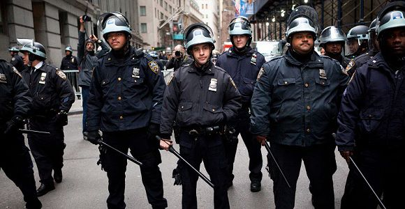 Caption: Police officers stand with their batons at the ready during a march of Occupy Wall Street protestors on the Financial District, Thursday, Nov. 17, 2011, in New York. Two days after the encampment that sparked the global Occupy movement was cleared by authorities, demonstrators marched through the financial district and promised mass gatherings in other cities. (AP Photo/John Minchillo)