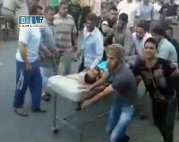 EDITOR'S NOTE: REUTERS CANNOT INDEPENDENTLY VERIFY CONTENT OF THE VIDEO FROM WHICH THIS STILL IMAGE WAS TAKEN. A man on a stretcher is carried to Al Badra Hospital in Hama in this still image taken from video July 31, 2011. Syrian army tanks firing shells and machineguns stormed the city of Hama on Sunday, killing at least 45 civilians in a move to crush demonstrations against President Bashar al-Assad's rule, residents and activists said. REUTERS/YouTube via Reuters TV (SYRIA - Tags: CIVIL UNREST POLITICS) FOR EDITORIAL USE ONLY. NOT FOR SALE FOR MARKETING OR ADVERTISING CAMPAIGNS