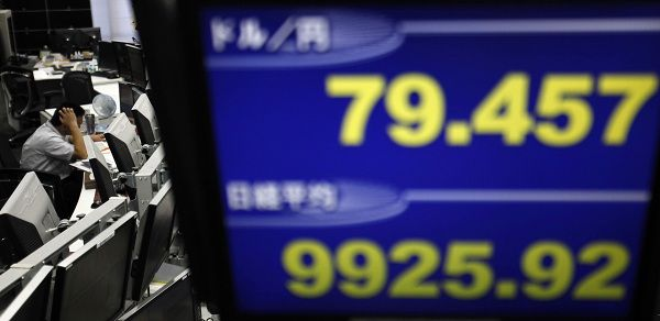 An employee of a foreign exchange trading company works behind a monitor displaying the Japanese Yen's exchange rate against the U.S. dollar (top) and Nikkei share average in Tokyo July 12, 2011. The Nikkei average lost 1.4 percent on Tuesday in its biggest fall in a month, slipping below support at 10,000 as financial stocks tumbled on concern that the euro zone's debt woes may spread to Italy and over a stalemate in U.S. budget talks. REUTERS/Toru Hanai (JAPAN - Tags: BUSINESS)
