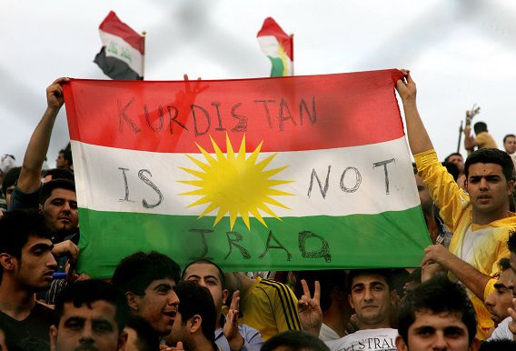 A picture taken from behind a fence shows Iraqi Kurdish fans holding a Kurdistan flag bearing a slogan as an Iraqi national flag flies during the AFC Cup final football match between Arbil club and Kuwait SC in the Iraqi city of Arbil on November 3, 2012. Kuwait SC won the match 4-0 for AFC CUP championship. AFP PHOTO/SAFIN HAMED