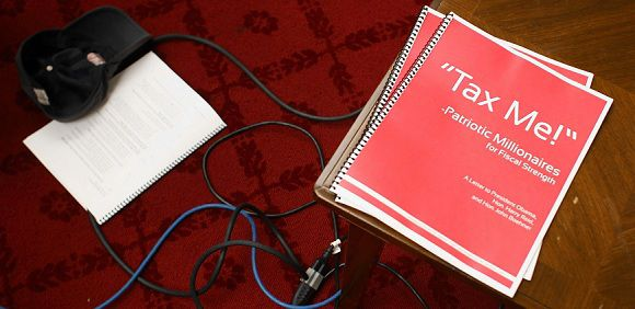 "Caption: WASHINGTON, DC - NOVEMBER 16: A ""Tax Me"" booklet lies on table during a news conference where millionaires asked Congress to raise taxes on Capitol Hill November 16, 2011 in Washington, DC. A group called ""Millionaires for Fiscal Strength"" hosted the news conference to call on the Congressional super committee to raise taxes on people with incomes over $1 million. Mark Wilson/Getty Images/AFP"